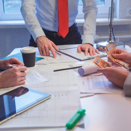 Close-up of Business people discussing a financial plan. Business meeting at the office. Payment for company services in cash. The customer in the office of the contractor